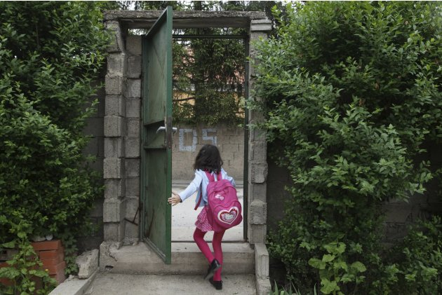 Koshi leaves through the main door in the garden of her house in the ethnically divided town of Mitrovica