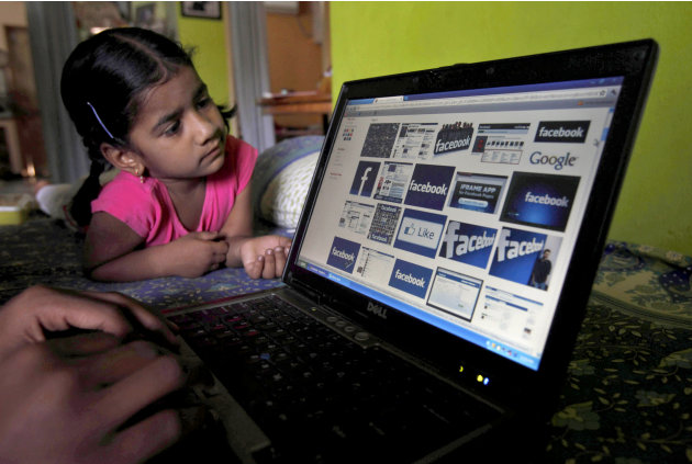 FILE- In this Friday, May 18, 2012, file photo, a child  looks at a laptop displaying Facebook logos in Hyderabad, India. Facebook said Monday, June 4, 2012, it is testing out ways to allow younger ki