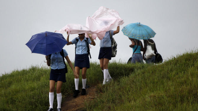 Students cover themselves from rains caused by the approaching of Hurricane Paula in Los Palacios, Cuba, Wednesday, Oct. 13, 2010. (AP Photo/Javier Galeano)