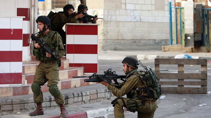 Israeli army soldiers take positions during clashes with Palestinians in an early morning operation in the West Bank city of Jenin, Wednesday, July 2, 2014. Tensions have mounted between Israel and the Palestinians after the bodies of three Israeli teens were found in the West Bank more than two weeks after they went missing. (AP Photo/Mohammed Ballas)