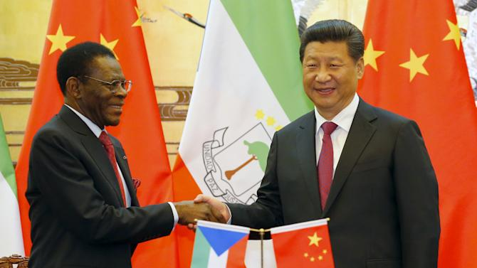 Equatorial Guinea's President Mbasogo shakes hands with Chinese President Xi during a signing ceremony at the Great Hall of the People in Beijing