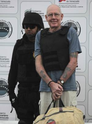 US citizen Scott Harris is escorted by a police officer during his deportation to the US at the Simon Bolivar airport in Maiquetia, near Caracas, Venezuela, Monday, Sept. 19, 2011. Harris is suspected of smuggling illegal drugs to the United States and Europe.(AP Photo/Fernando Llano)