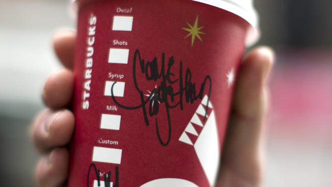 "Justin McCartney of Hampton, Va., holds up a cup with the words ""Come Together"" written on it outside a Starbucks cafe in Washington, Thursday, Dec. 27, 2012. Starbucks is using its coffee cups to jump into the political fray in Washington. The world's biggest coffee chain is asking employees at cafes in the Washington area to scribble the words ""Come Together"" on cups for drink orders on Thursday and Friday. CEO Howard Schultz says the words are intended as a message to lawmakers about the damage being caused by the divisive negotiations over the ""fiscal cliff.""  (AP Photo/ Evan Vucci)"
