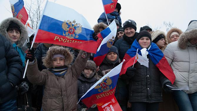 In this photo provided by Olympictorch2014.com, citizens welcome the Olympic torch relay in Rostov-on-Don, a city about 1,000 kilometers (600 miles) south of Moscow, Russia, Wednesday, Jan. 22, 2014. The 65,000-kilometer (40,389 mile) Sochi torch relay, which started on Oct. 7, is the longest in Olympic history. The torch has traveled to the North Pole on a Russian nuclear-powered icebreaker and has even been flown into space. (AP Photo/Olympictorch2014.com)