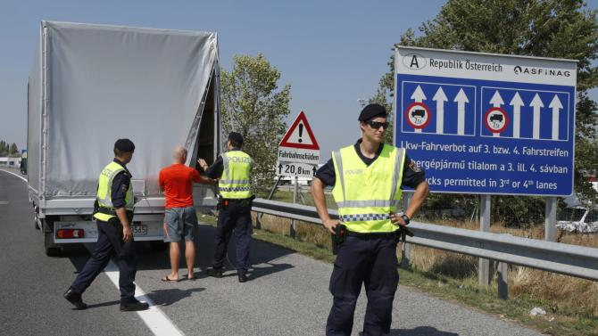Austrian police officers control cars arriving to Austria at a checkpoint in the village of Nickelsdorf