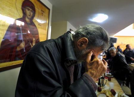File photo of a man praying at a free food distribution center in Athens