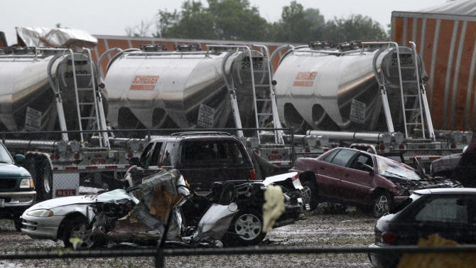 Destroyed vehicles sit in a Kenworth trailer lot after a tornado that swept through the area toppling many of the trailers on the lot Tuesday, April 3, 2012, in Lancaster, Texas. Tornadoes tore through the Dallas area Tuesday, peeling roofs off homes, tossing big-rig trucks into the air and leaving flattened tractor trailers strewn along highways and parking lots.  (AP Photo/Tony Gutierrez)