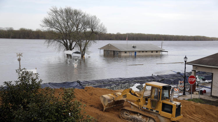 Heavy equipment is used in the effort to reinforce a temporary levee Monday, April 22, 2013, in Clarksville, Mo. The swollen Mississippi River has strained a hastily erected makeshift floodwall in Clarksville, creating two trouble spots that volunteers were scrambling to patch. (AP Photo/Jeff Roberson)