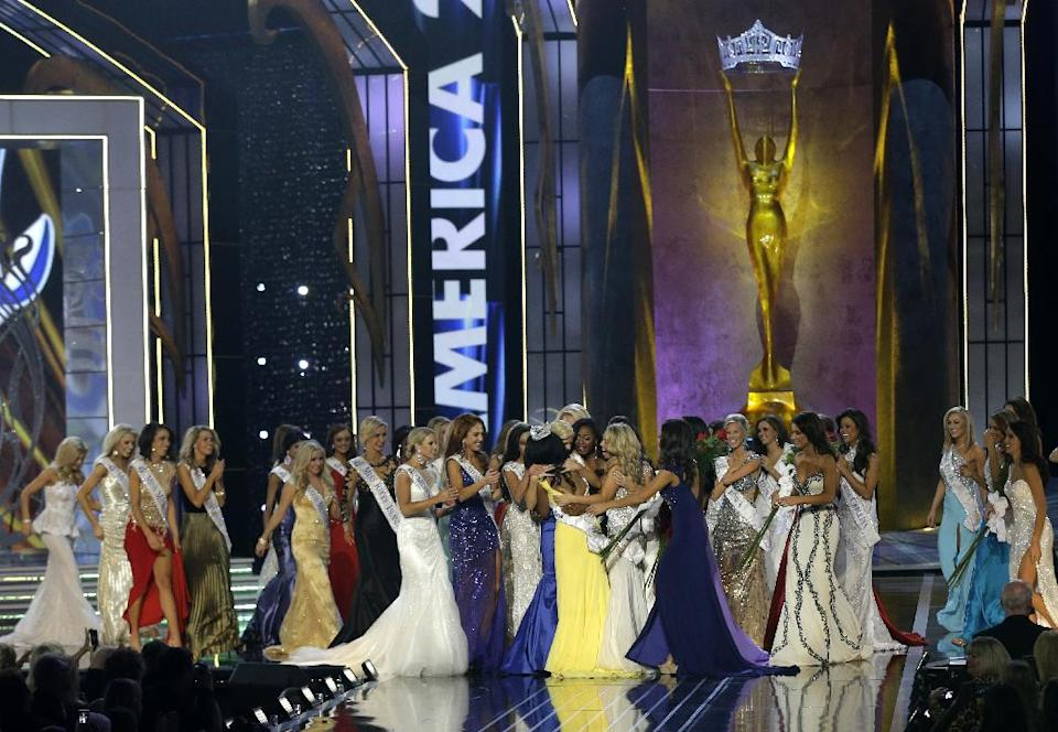 Miss New York Nina Davuluri, center left in yellow, is approached by contestants after Davuluri was crowned as Miss America 2014, Sunday, Sept. 15, 2013, in Atlantic City, N.J. (AP Photo/Mel Evans)