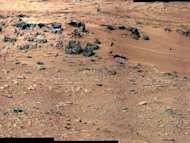 "This patch of windblown sand and dust downhill from a cluster of dark rocks is the ""Rocknest"" site, which has been selected as the likely location for first use of the scoop on the arm of NASA's Mars rover Curiosity. This view is a mosaic of im"
