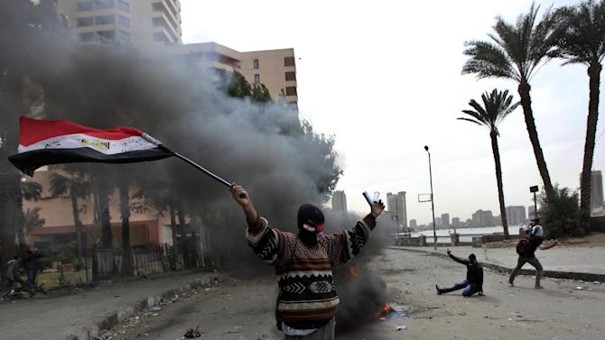 A protester hold the Egyptian national flag during clashes with riot police near Tahrir Square, Cairo, Egypt, Monday, Jan. 28, 2013. Health and security officials say a protester has been killed in clashes between rock-throwing demonstrators and police near Tahrir Square in central Cairo. The officials say the protester died Monday on the way to the hospital after being shot. (AP Photo/Khalil Hamra)