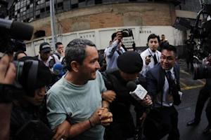 Lorenzana is escorted by the Guatemalan police after his arrest outside the Supreme Court of Justice in Guatemala City
