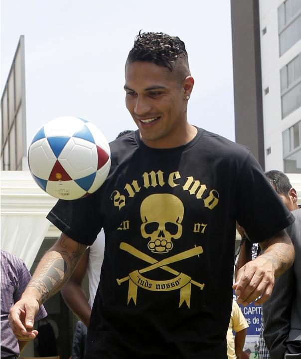 Peruvian soccer player Paolo Guerrero plays with children from soccer schools during a Christmas event in Lima