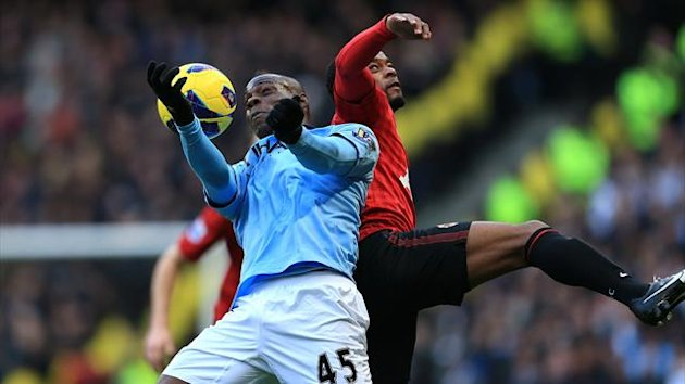 Manchester City's Mario Balotelli (left) and Manchester United's Patrice Evra (right) battle for the ball (PA Photos)