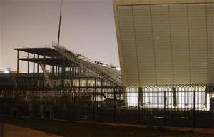 """Workers look at the Arena Sao Paulo stadium, known as """"Arena Corinthians"""" and """"Itaquerao"""", in Sao Paulo"""