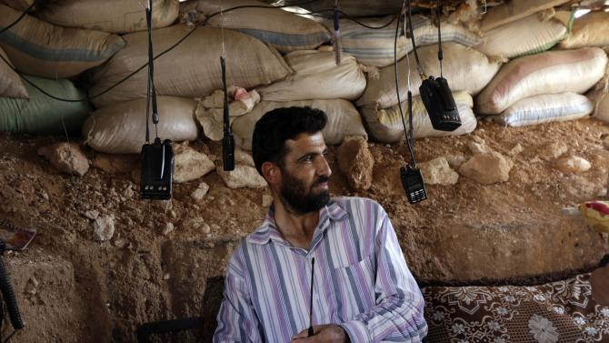 Free Syrian Army fighter listens to walkie-talkies on one of the front lines of Wadi Al-Daif camp in the southern Idlib countryside
