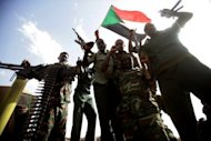 Sudanese soldiers wave guns and flags during President Omar al-Bashir&#39;s visit to Sudan&#39;s key oil centre of Heglig in April 2012. Neither the United Nations nor the African Union can impose its will on Sudan, Bashir has said, after fresh fighting along the border with South Sudan