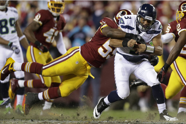 Seattle Seahawks quarterback Russell Wilson is stopped by Washington Redskins inside linebacker London Fletcher during the first half of an NFL wild card playoff football game in Landover, Md., Sunday