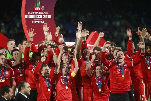 Philipp Lahm of Germany's Bayern Munich holds the trophy as he celebrates with his team mates after winning their 2013 FIFA Club World Cup final soccer match against Morocco's Raja Casablanca