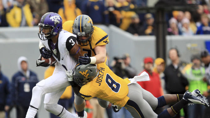 West Virginia's Jared Barber (33) and Karl Joseph (8) tackle TCU's Brandon Carter (3) during the first half of their NCAA college football game in Morgantown, W.Va., on Saturday, Nov. 3, 2012. (AP Photo/Christopher Jackson)