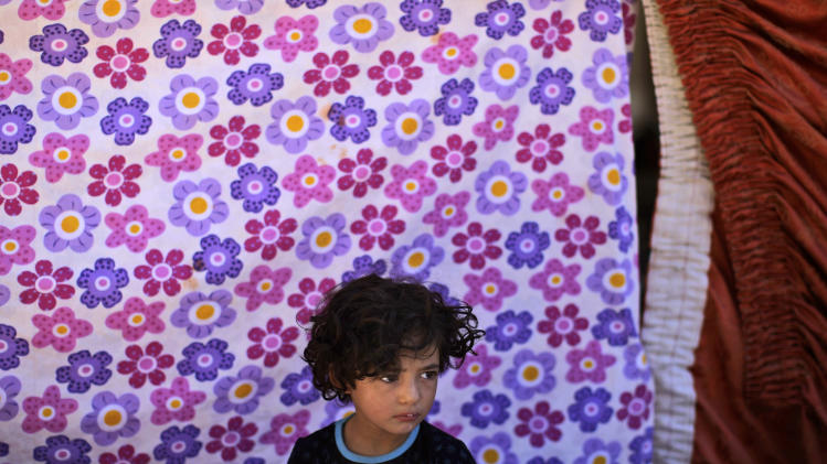 A Syrian girl, who fled her home with her family due to fighting between the Syrian army and the rebels, takes refuge at the Bab Al-Salameh border crossing, in her family's preparations to enter one of the refugee camps in Turkey, near the Syrian town of Azaz, Thursday, Aug. 23, 2012. Thousands of Syrians who have been displaced by the country's civil are struggling to find safe shelter while shelling and airstrikes by government forces continue. (AP Photo/Muhammed Muheisen)