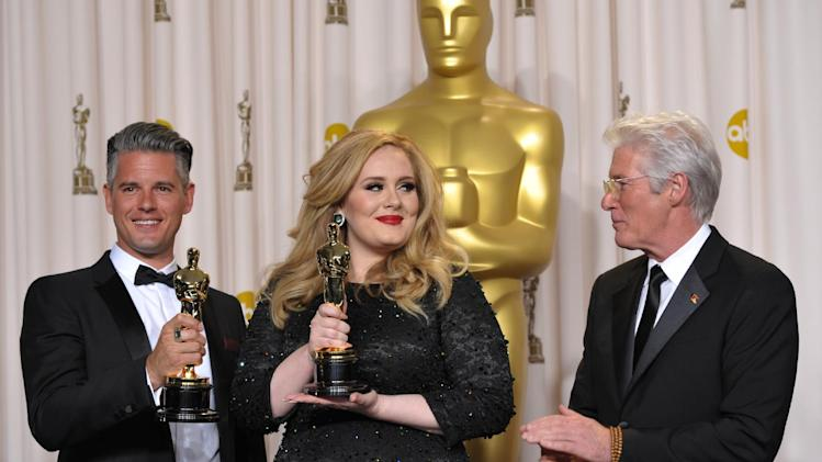"Adele and Paul Epworth pose with their award for best original song for ""Skyfall"" with presenter Richard Gere during the Oscars at the Dolby Theatre on Sunday Feb. 24, 2013, in Los Angeles. (Photo by John Shearer/Invision/AP)"