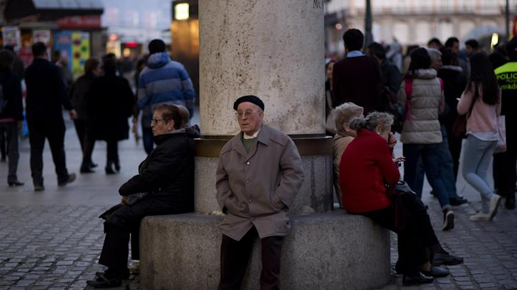 People sit in a public bench in Puerta del Sol square in Madrid, Spain, Thursday, March. 13, 2014. (AP Photo/Emilio Morenatti)