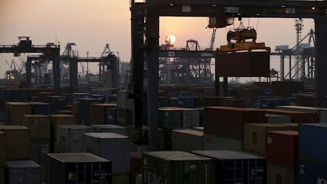 A crane moves a container during sunset at Koja Container Terminal near Tanjung Priok port in Jakarta
