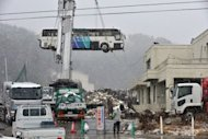 A bus is removed from a roof of a building in Ogatsu district in Ishinomaki, Miyagi prefecture on March 10, 2012. Politicians from the devastated northeast repeatedly express exasperation at the slow pace of reconstruction after the tsunami and a lack of leadership from Tokyo