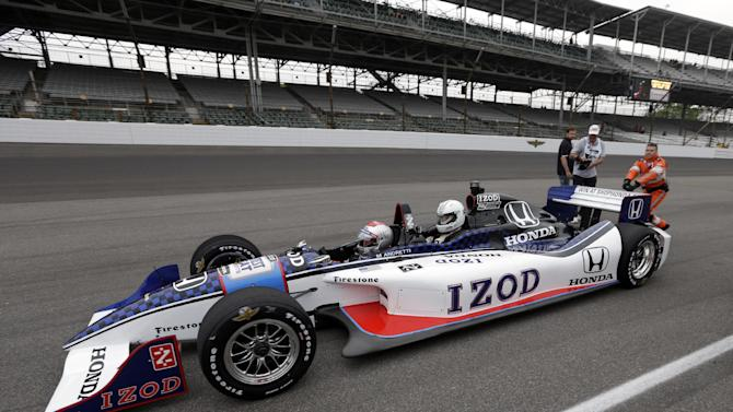 Indianapolis Colts head coach Chuck Pagano, seated right, leaves the pit area in a two-seat IndyCar driven by 1969 Indy 500 champion Mario Andretti on the first day of qualifications for the Indianapolis 500 auto race at the Indianapolis Motor Speedway in Indianapolis, Saturday, May 18, 2013. (AP Photo/Darron Cummings)