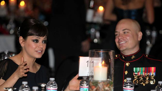 Sgt. Scott Moore and his guest, actress Mila Kunis stand during the National Anthem at the 236th Marine Corps birthday ball for 3rd Battalion, 2nd Marine Regiment, 2nd Marine Division in Greenville, N.C., on Friday Nov. 18, 2011. (AP Photo/Marine Corps., Cpl. Johnny Merkley)