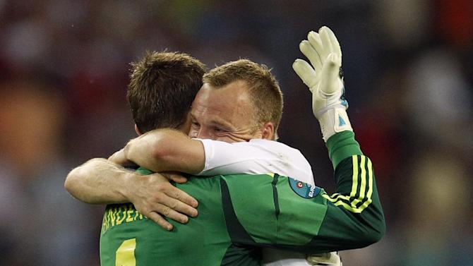 Denmark goalkeeper Stephan Andersen and Lars Jacobsen embrace after the Euro 2012 soccer championship Group B match between the Netherlands and Denmark in Kharkiv , Ukraine, Saturday, June 9, 2012. Denmark won the match 1-0. (AP Photo/Matthias Schrader)