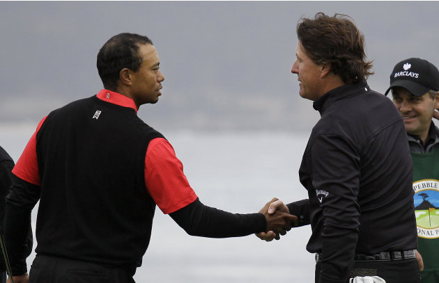 Tiger Woods, left, shakes hands with Phil MIckelson on the 18th green at Pebble Beach Golf Links during the final round of the AT&T Pebble Beach National Pro-Am golf tournament in Pebble Beach, Calif.