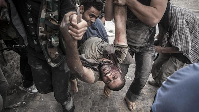 In this Saturday, Oct. 20, 2012 photo, Free Syrian Army fighters carry a civilian away from the line-of-fire after he was shot twice, in his stomach and back, by a Syrian army sniper while walking near the frontline in the Bustan al-Qasr neighborhood of Aleppo, Syria. (AP Photo/Narciso Contreras)