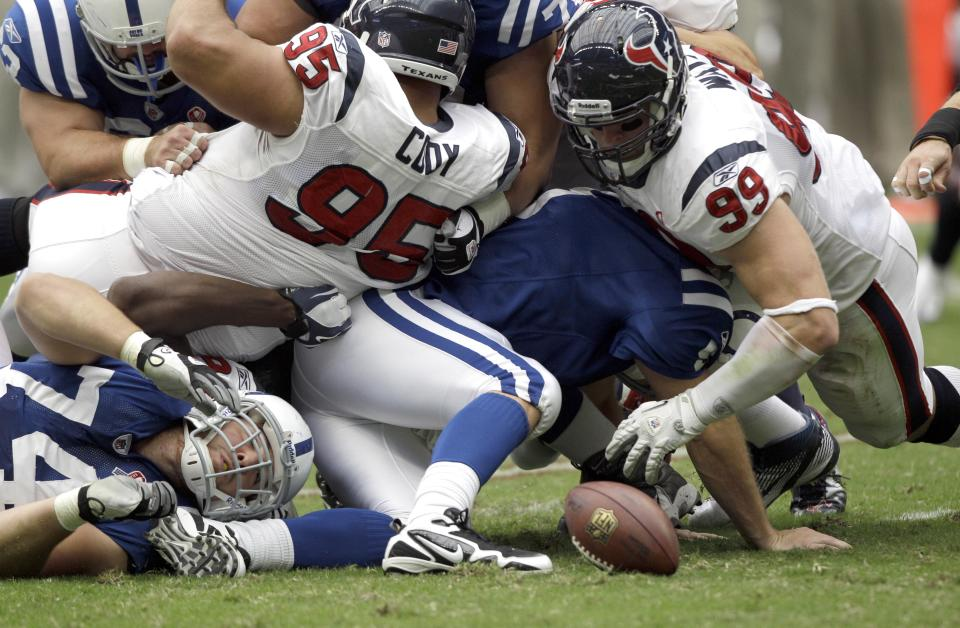 Indianapolis Colts quarterback Kerry Collins, bottom center, fumbles the snap as Houston Texans defensive end J.J. Watt (99) tackles him in the first quarter of an NFL football game Sunday, Sept. 11, 2011, in Houston. Watt recovered the fumble. (AP Photo/David J. Phillip)