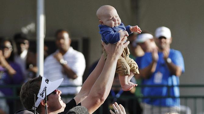 Charlie Beljan, left, and his wife Merisa, right, hold up their son Graham on the 18th green following Charlie's win at the Children's Miracle Network Hospitals golf tournament in Lake Buena Vista, Fla., Sunday, Nov. 11, 2012. (AP Photo/Reinhold Matay)