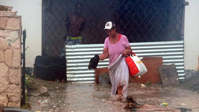 A woman wades through flood water brought by Hurricane Sandy as she evacuates her home in the Caribbean Terrace neighborhood of eastern Kingston, Jamaica, Wednesday, Oct. 24, 2012.  Hurricane Sandy pounded Jamaica with heavy rain as it headed for landfall near the country's most populous city on a track that would carry it across the Caribbean island to Cuba, and a possible threat to Florida.  (AP Photo/Collin Reid)