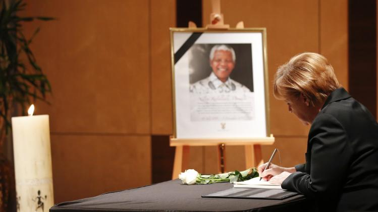 German Chancellor Merkel writes her condolences in a book for late former South African President Nelson Mandela at South Africa's embassy in Berlin