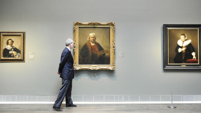 "This May 30, 2012 photo shows Museum of Fine Arts, Houston curator Edgar Peters Bowron passing Rembrandt's ""Portrait of the Artist"", center, as he looks over some of the paintings from London's Kenwood House at the museum in Houston. The collection of paintings including works by Rembrandt, Van Dyck and Gainsborough has left its home to travel the U.S. while the stately mansion on Hampstead Heath undergoes renovation. The exhibit opens June 3. (AP Photo/Pat Sullivan)"
