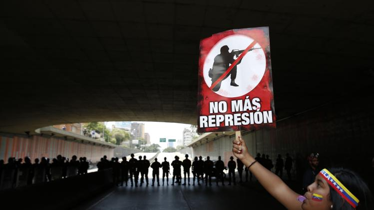 Anti-government protester holds a placard reading:'stop repression' in front of police during a march in Caracas