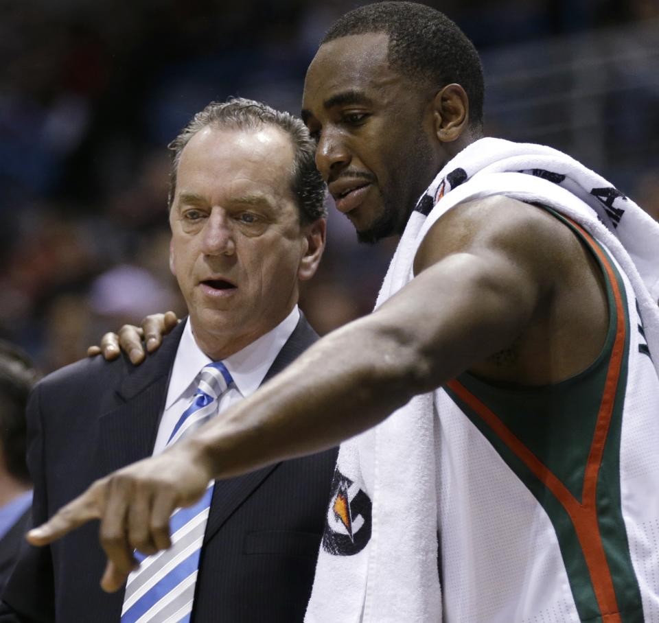 Milwaukee Bucks coach Jim Boylan talks with Luc Richard Mbah a Moute, right, during the first half of an NBA basketball game against the Phoenix Suns on Tuesday, Jan. 8, 2013, in Milwaukee. (AP Photo/Jeffrey Phelps)