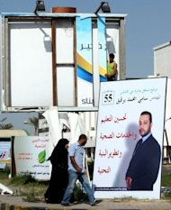 A Libyan couple walk past an election campaign poster for an independent candidate as a worker puts up a billboard in Tripoli on July 1