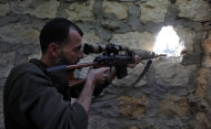 In this Wednesday, Nov. 14, 2012 file photo, a rebel sniper aims at a Syrian army position on the outskirts of Aleppo, Syria. Through mid-2012, rebel power grew and Assad&#39;s army ramped up its response. Relentless government shelling leveled neighborhoods and killed hundreds. Regular reports emerged of mass killings by the regime or thugs loyal to it, pushing more Syrians toward armed struggle. The government, which considers the opposition terrorist gangs backed by foreign powers, denied any role, and does not respond to requests for comment on its military. The rebels, too, were accused of atrocities. (AP Photo/ Khalil Hamra, File)