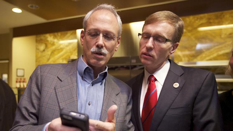 Republican candidate for Washington Governor, Rob McKenna, right, looks at election returns with supporter Gary Smith of Seattle, Tuesday, Nov. 6, 2012, in Bellevue, Wash. At the time he spoke, the race between McKenna and Democrat Jay Inslee remained too close to call. (AP Photo/Stephen Brashear)