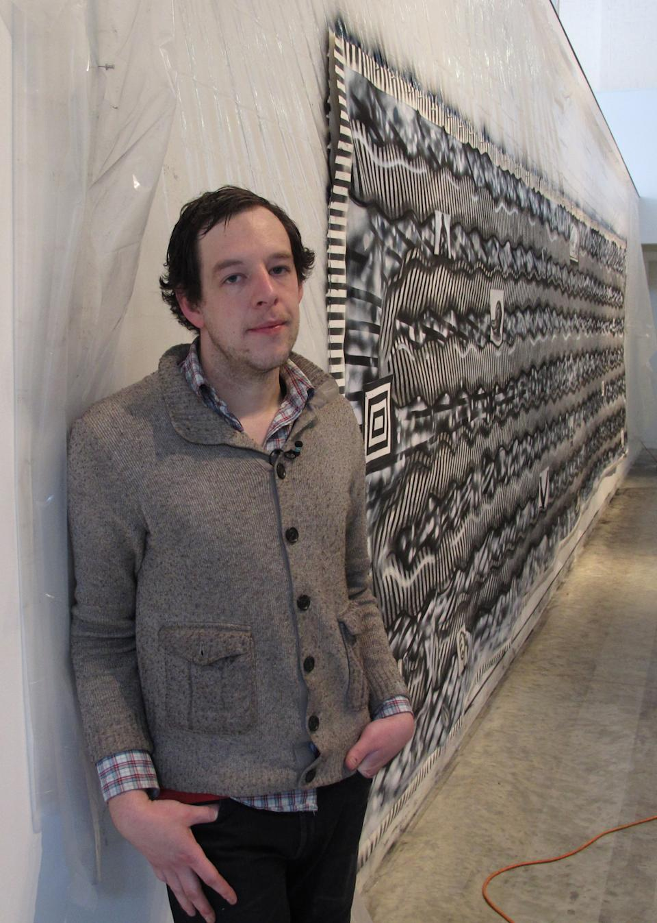 In this Wednesday, Feb. 19, 2013 photo, Ryan Travis Christian stands beside a mural he created over the course of 12 days in the emerging artist gallery at the Contemporary Art Museum in Raleigh, N.C. The Chicago artist completely reworked the wall-sized drawing several days into his first museum exhibition. (AP Photo/Allen Breed)