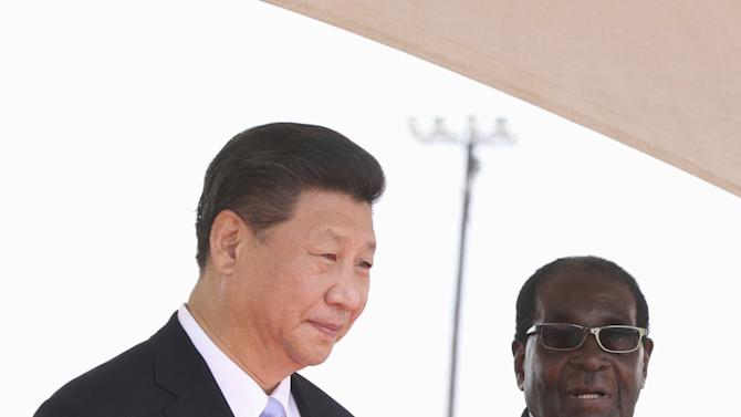 Chinese President Xi Jinping talks with Zimbabwean President Robert Mugabe on arrival for a state visit in Harare, Zimbabwe