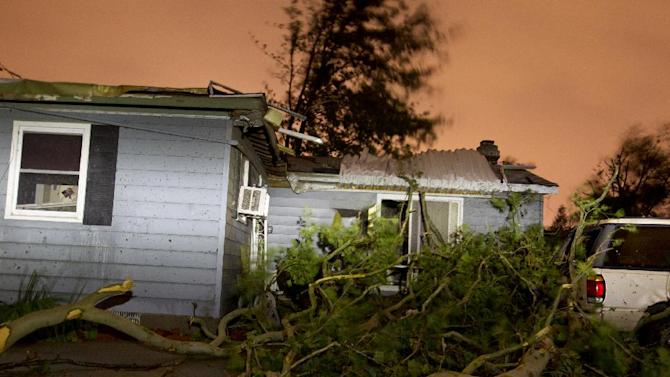 A house is damaged as heavy winds brought down trees during a severe storm late Sunday, July 6, 2014 in Kentwood, Mich. A severe thunderstorm packing winds estimated at more than 80 mph injured several people and caused significant damage to homes in western Michigan. (AP Photo/The Grand Rapids Press, Joel Bissell) ALL LOCAL TELEVISION OUT; LOCAL TELEVISION INTERNET OUT