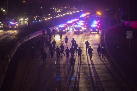 California Highway Patrol officers walk to clear the 101 freeway from protesters in Los Angeles