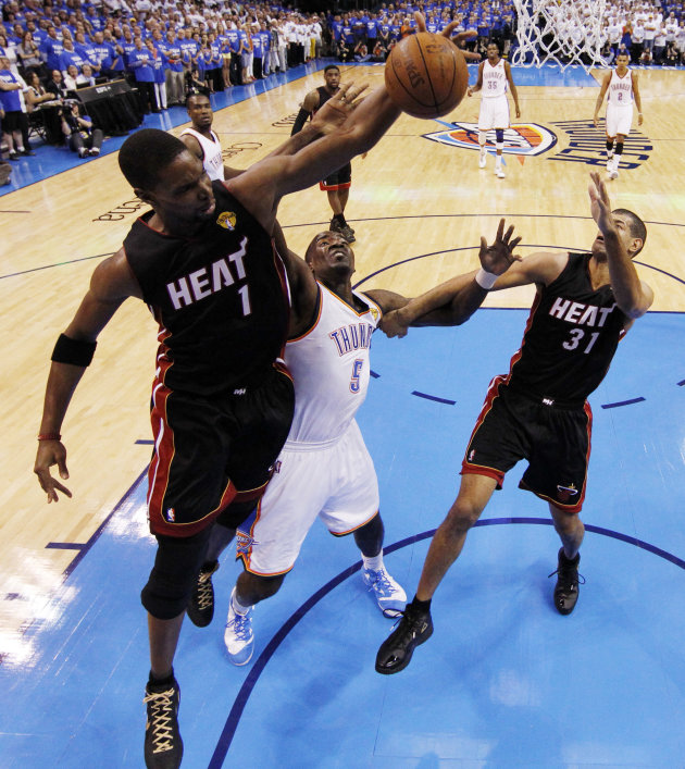 Miami Heat power forward Chris Bosh  and Oklahoma City Thunder center Kendrick Perkins (5) go after a rebound as small forward Shane Battier moves in during the first half at Game 2 of the NBA finals