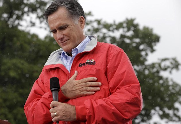 Republican presidential candidate, former Massachusetts Gov. Mitt Romney puts his hand on his heart during a moment of silence for the embassy officials killed in Libya, as he campaigns in the rain at Lake Erie College in Painesville, Ohio, Friday, Sept. 14, 2012. (AP Photo/Charles Dharapak)